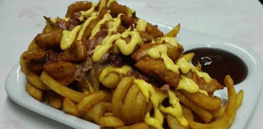 Необычный картофель головокружения (приправленный луком), хрустящий бекон, полоски курицы в панировке и растопленный чеддер, все в сопровождении соуса для барбекю.