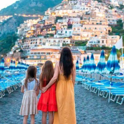 Семья обнималась на пляже побережья Амальфи, глядя на Позитано