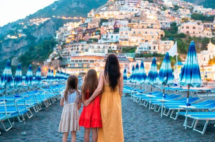 Famiglia abbracciata sulla spiaggia della costiera amalfitana guardando verso positano