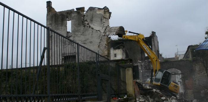 foto dei una ruspa al lavoro per rimuovere i detriti del crollo di un muro a san giovanni a teduccio