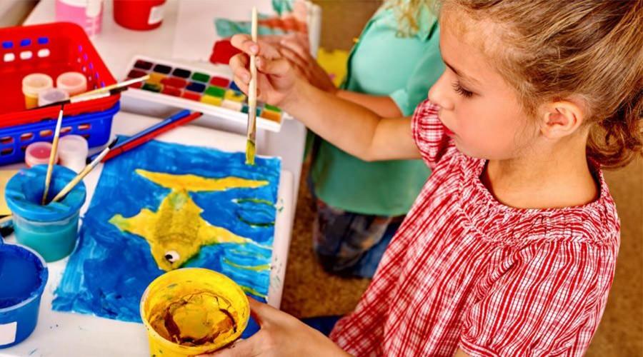 Bambina che usa i colori per disegnare