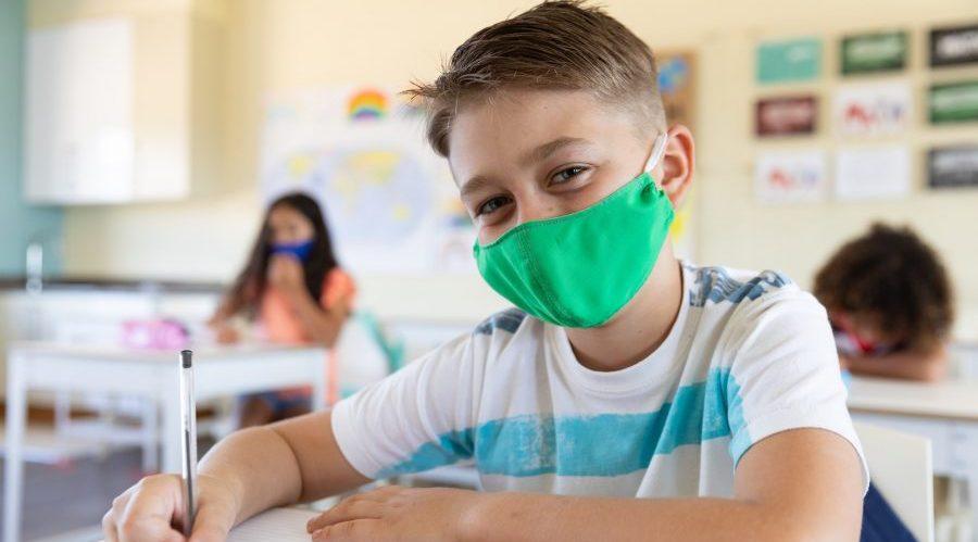 Bambino a scuola con la mascherina